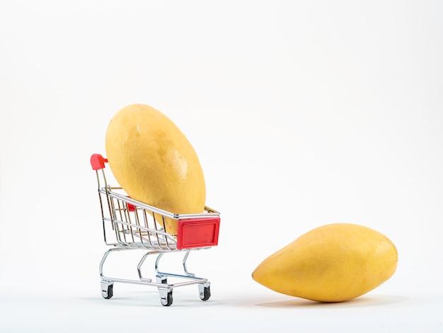 Rijp mango's het winkelen concept met boodschappenwagentje, mand op de witte achtergrond