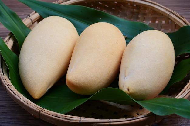 Rijp mango'sfruit in mand met bladeren