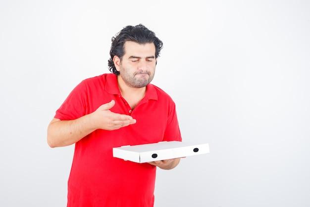 Rijp mannetje dat in rood t-shirt geopende pizzadoos bekijkt en verrukt, vooraanzicht kijkt.