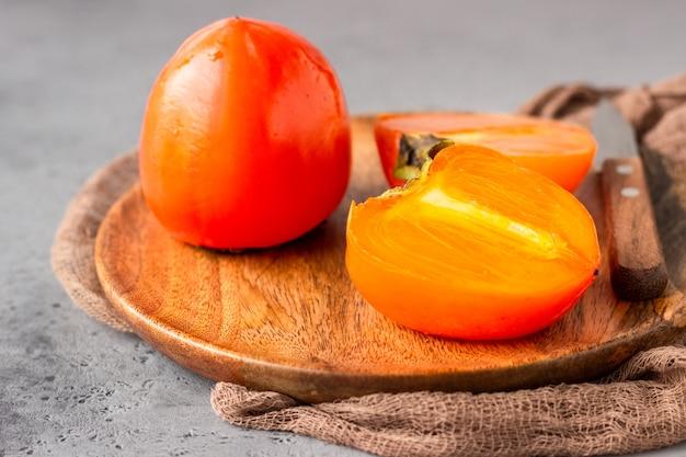 Rijp oranje dadelpruimfruit met mes op een houten plaat. gezond eten.