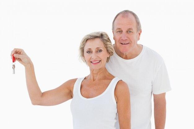 Rijp paar dat bij camera met nieuw huissleutel glimlacht