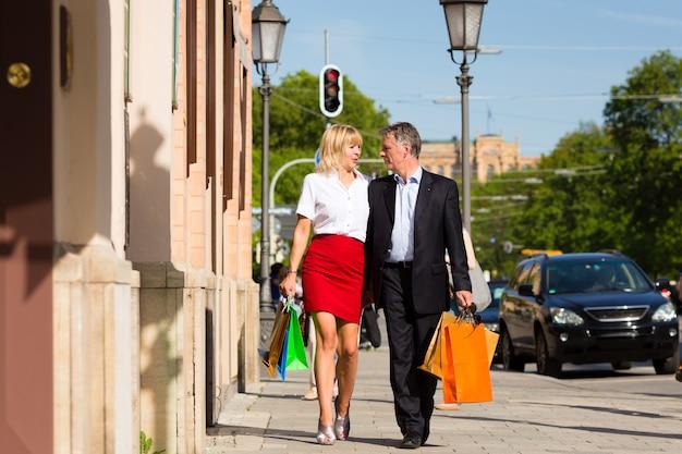 Rijp paar dat door stad wandelt die in de lente winkelt