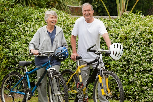Rijp paar dat met hun fietsen loopt