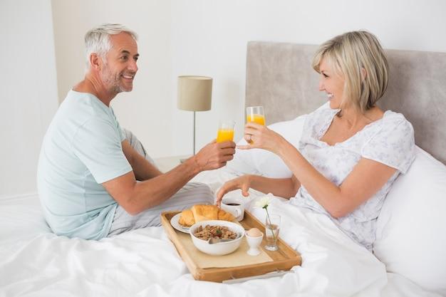 Rijp paar dat ontbijt in bed heeft