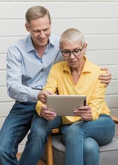 Rijp paar dat op een tablet kijkt