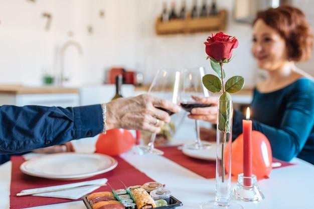 Rijp paar die een romantisch diner hebben thuis voor valentijnskaartendag en toost met rode wijn doen