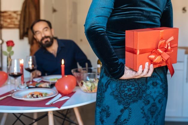 Rijp paar die een romantisch diner hebben thuis voor valentijnskaartendag met verrassingsgift