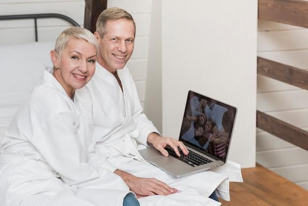 Rijp paar die samen thuis foto's op hun laptop bekijken