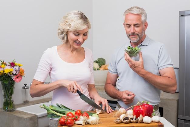 Rijp paar die voedsel samen in keuken voorbereiden