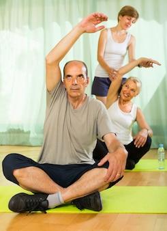 Rijp paar met trainer bij gymnastiek