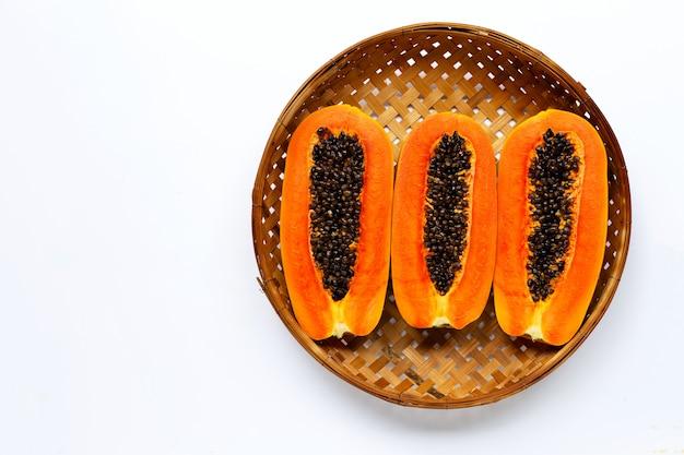 Rijp papajafruit in houten bamboe dorsende mand op witte achtergrond.