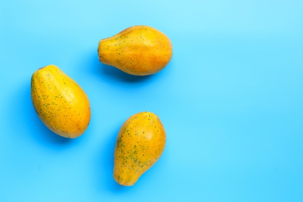 Rijp papajafruit op blauwe achtergrond. kopieer ruimte