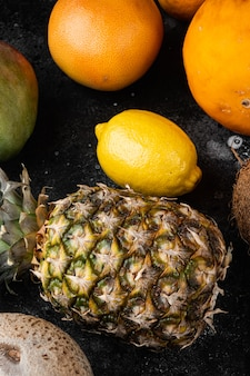 Rijp, sappig vers tropisch fruit, op zwarte donkere stenen tafelachtergrond, bovenaanzicht plat gelegd