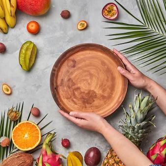 Rijp tropisch fruit, kokos, mango, carambola's, lychee en palmbladeren op een grijze betonnen ondergrond. de handen van de vrouw houden een leeg bruin rond bord vast met een kopie van de ruimte. plat leggen