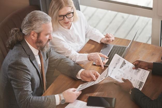 Rijp zakenpaar dat financieel document bespreekt met partner tijdens vergadering in café