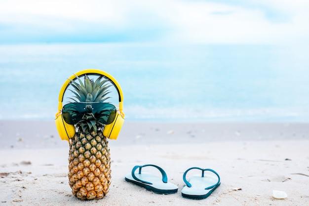 Rijpe aantrekkelijke ananas in stijlvolle gespiegelde zonnebril en gouden koptelefoon op zand tegen turquoise zeewater. tropische zomervakantie concept.