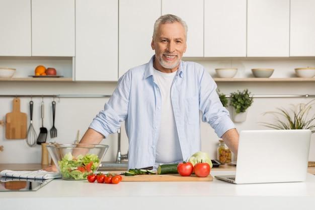Rijpe aantrekkelijke mens die zich bij keuken het koken bevindt