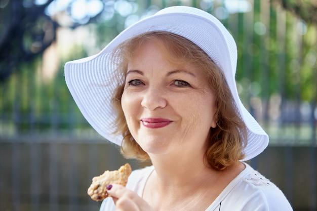 Rijpe aantrekkelijke vrouw met hoed poseert buiten, kaukasische dame van middelbare leeftijd in hoofdtooi lacht