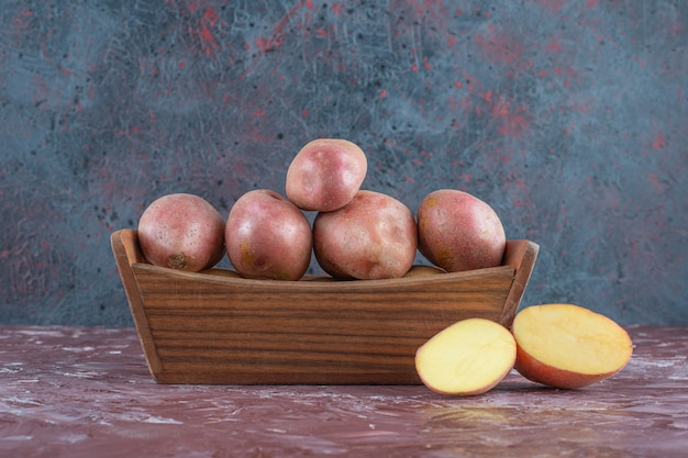 Rijpe aardappelen in een houten kist, op de marmeren achtergrond.