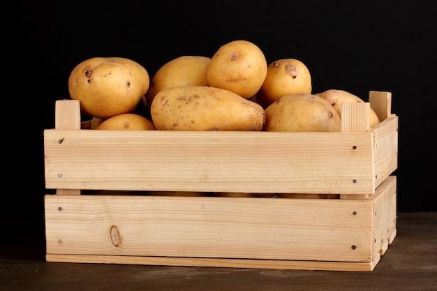 Rijpe aardappelen in houten kist op houten tafel op zwarte ruimte