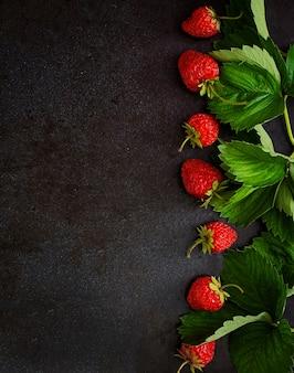 Rijpe aardbeien en bladeren op zwarte achtergrond. bovenaanzicht