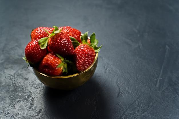 Rijpe aardbeien in een gouden kom.