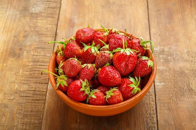 Rijpe aardbeien in een rieten mand op een houten ondergrond.