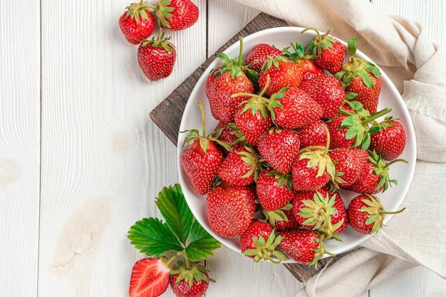 Rijpe aardbeien in een witte plaat op een lichte achtergrond