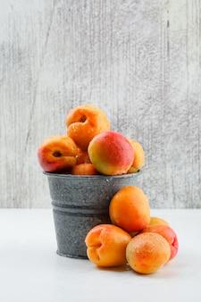 Rijpe abrikozen in een mini-emmer. zijaanzicht.