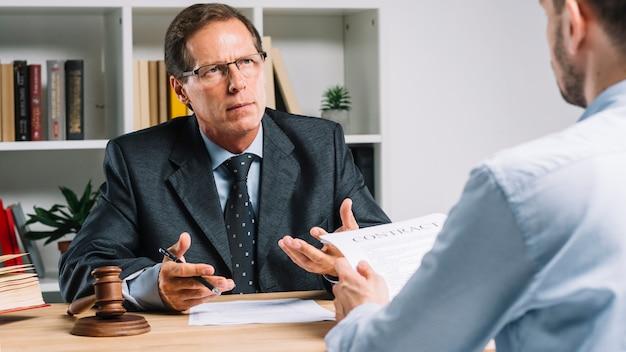 Rijpe advocaat die contract bespreken met cliënt in de rechtszaal