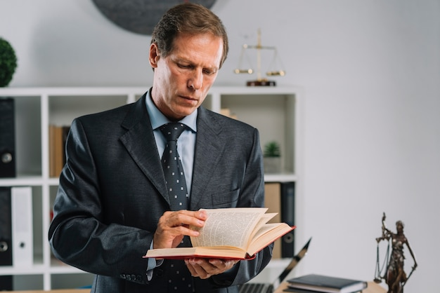 Rijpe advocaat die pagina's van wetsboek in de rechtszaal draaien