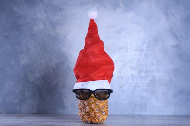 Rijpe ananas, ananas met zonnebril in kerstmuts. nieuwjaar fruit concept