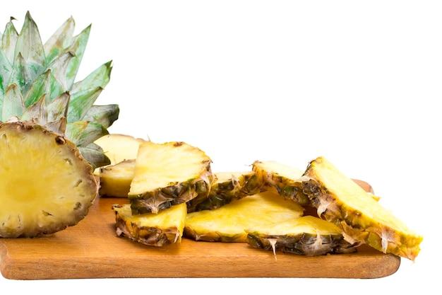 Rijpe ananas en ananasschijfjes op een houten achtergrond tropisch fruit.