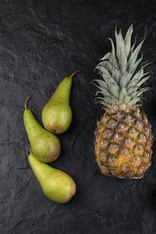 Rijpe ananas en drie verse peren op zwarte ondergrond