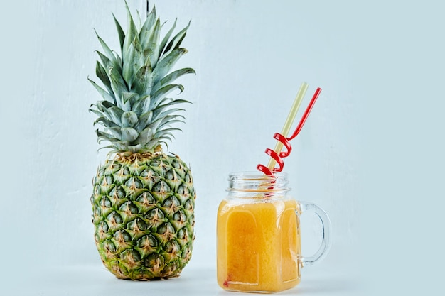 Rijpe ananas en een glas sap op blauw.