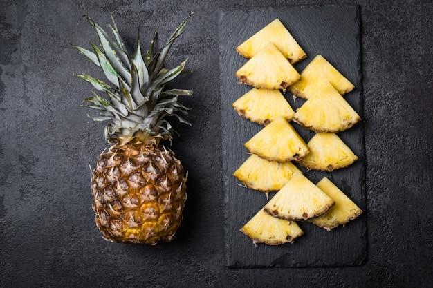 Rijpe ananas en plakjes op een zwarte achtergrond