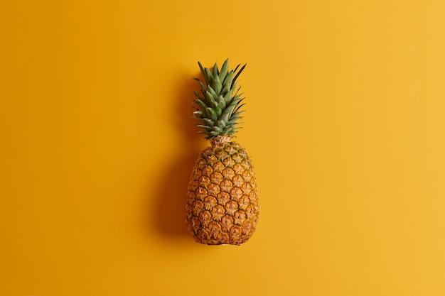 Rijpe ananas geïsoleerd op gele achtergrond. exotisch fruit met weinig calorieën, boordevol voedingsstoffen en antioxidanten, kan op verschillende manieren worden geconsumeerd of aan uw dieet worden toegevoegd. ingrediënt voor het maken van sap