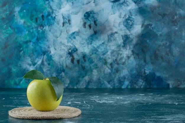 Rijpe appel op een onderzetter, op de marmeren tafel.