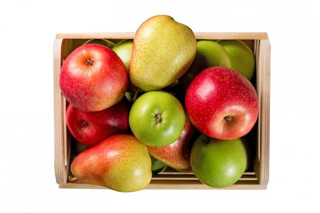 Rijpe appels en peren in een houten doos die op witte achtergrond wordt geïsoleerd.