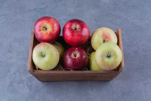 Rijpe appels in doos op marmeren tafel.