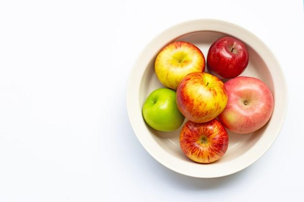 Rijpe appels in kom op witte achtergrond. bovenaanzicht