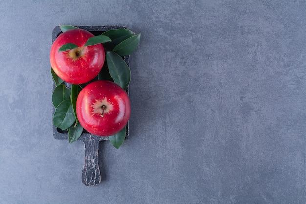 Rijpe appels met bladeren aan boord op marmeren tafel.