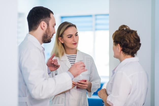 Rijpe arts die met verpleegsters in een gangziekenhuis bespreekt