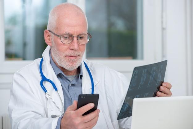 Rijpe arts die x-ray beeld bekijkt en telefoon met behulp van
