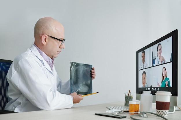 Rijpe arts in witte jas zittend aan tafel wijzend op röntgenfoto en bespreken met zijn collega's tijdens online conferentie