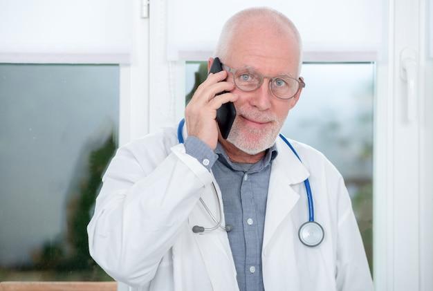 Rijpe arts op telefoon in zijn kantoor