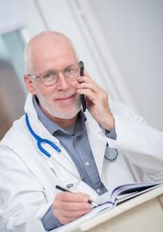 Rijpe arts op telefoon op zijn kantoor