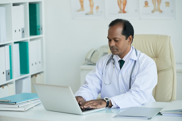 Rijpe arts sitting at desk die aan laptop werken