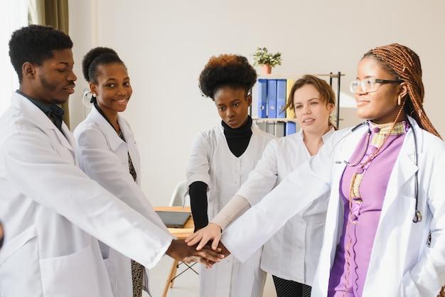 Rijpe artsen en jonge verpleegsters die handen samen in het ziekenhuis stapelen.