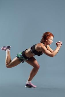 Rijpe atletische roodharige vrouw in sportkleding t-shirt en korte broek fitness oefeningen, grijze studioruimte